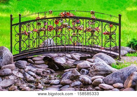 Footbridge with locks in the park. Decorative element of park and garden equipment.
