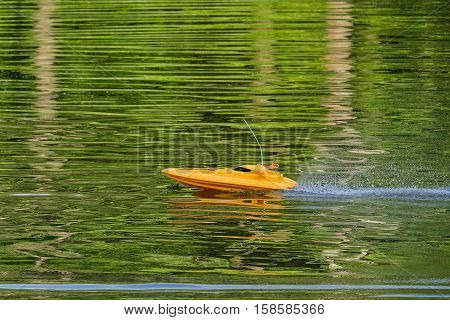 Yellow speedboat on remote control rushing on water surface