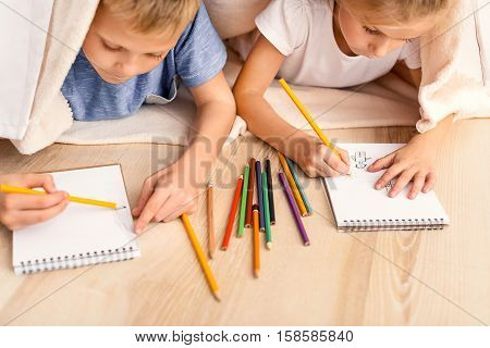 Lets depict our parents. Close up of cute little children drawing diligently with pencils while lying on floor in playroom