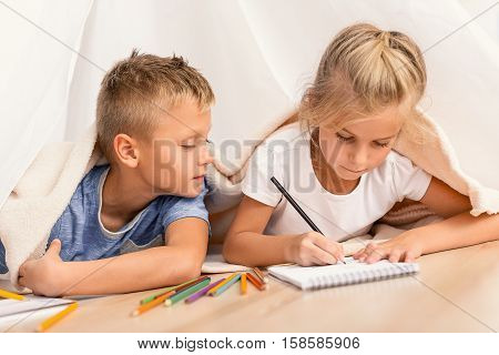 Very nice picture. Little cute girl drawing with pencil in notebook while lying on floor. Brother looking at picture, being near his sister