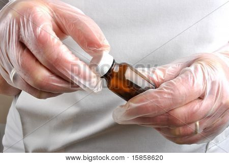 Health Care Staff With Disposable Glove Open Pill Bottle