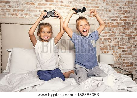 Time to entertainment. Pretty little girl and boy playing videogame, holding game controllers and laughing while sitting on bed. Small kids winning