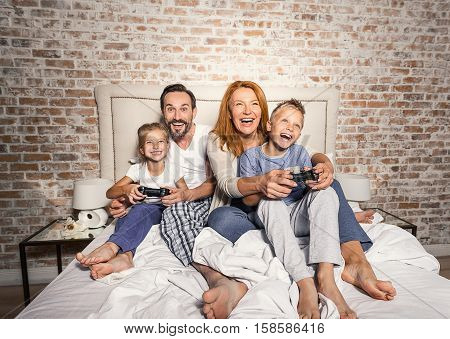 Fun times together. Mature smiling parents playing on console with their children enthusiastically while sitting on bed at home