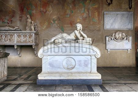 PISA, ITALY - JANUARY 9, 2016: Tomb sculptures on marble tomb in a medieval Memorial Camposanto Cemetery, Pisa, Italy