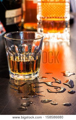 The word Yes written with spoiled whiskey on a bar counter