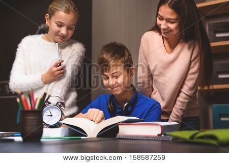 Attentive boy is sitting at table and reading book. Girls are standing behind him. They looking in text with smiles