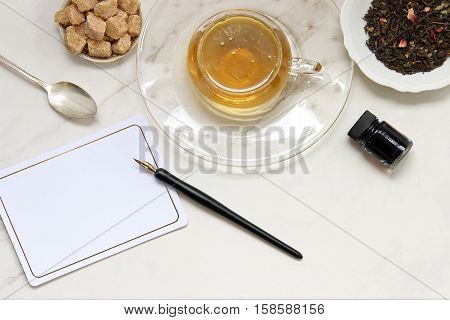 Over head flat lay view of golden herbal tea, loose tea leaves, raw sugar cubes, vintage spoon, vintage pen and ink, blank notecard. Open space for copy.