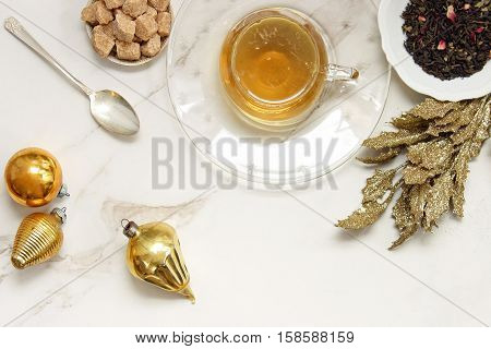 Over head flat lay view of golden herbal tea, loose tea leaves, raw sugar cubes, vintage spoon, vintage ornaments and golden leaves. Open space for copy.