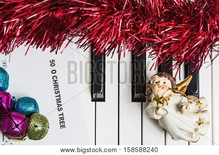 Christmas music concept. Printed music on the pianto with jingle bells angel and spangle.