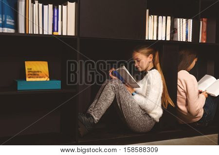 Two fascinated girls are sitting on shelves with open volumes