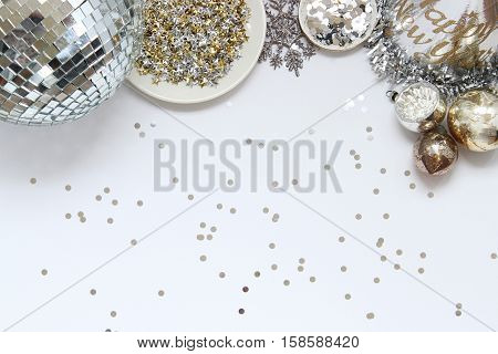 Over head flat lay view of New Year's Eve party supplies. Party hat, disco ball, stars confetti, and vintage ornaments border open space.