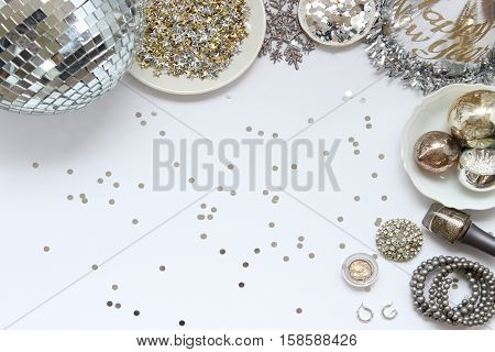 Over head flat lay view of New Year's Eve party supplies and makeup and jewelry. Party hat, disco ball, stars confetti, and vintage ornaments border open space.
