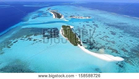 Panoramic landscape seascape aerial view over a Maldives Male Atoll islands. White sandy beach seen from above.