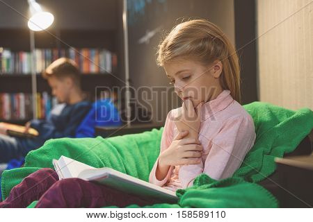 Attentive girl is sitting in comfortable bag chair and holding open volume