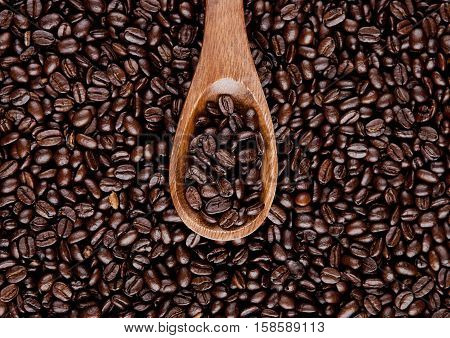 Wooden spoon with coffee been texture on beens background