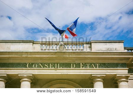 French and Eu Flag over Conseil d'Etat - Council of State building with French flag and Europena Union Flag in Paris France.