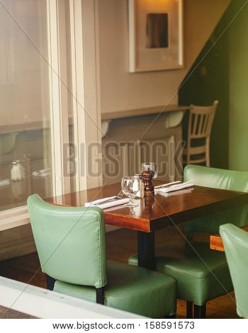 Old fashioned and cosy cafe - restaurant interior with leather chairs and wooden tables with sun illumination from the window
