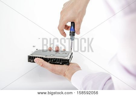 Man's hand holds 3.5 HDD. His another hand unscrews the hard drive case with a screwdriver. Isolated on white background.