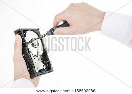 Man's hand holds open 3.5 HDD. His another hand unscrews the cover of the engine with a screwdriver. Isolated on white background.