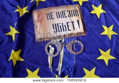 EU and Ukraine Flag with Vintage looking yellow Danger do not enter warning sign (RU)