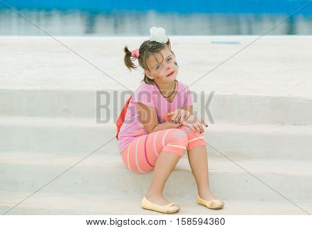 beautiful calm little girl with painted face sitting on the steps near the swimming pool