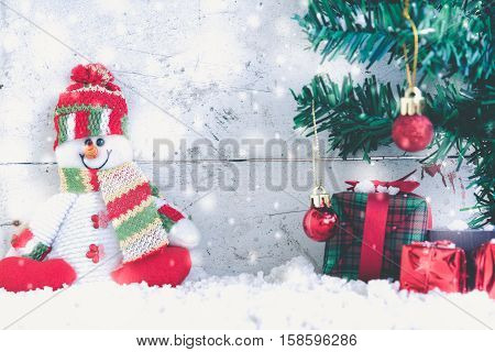 Snowman and snowfall with decorate fir tree on christmas day with copy space for season greeting
