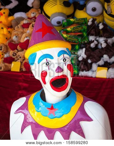 A colorful arcade clown with prizes stacked behind him.
