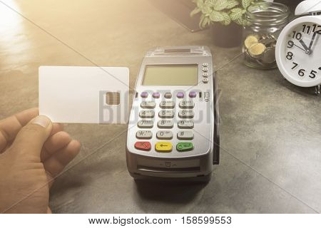 Hand On Hoing Credit Card Terminal Or Edc On Cashier  Table In The Store , Clock,coins In The Bottle