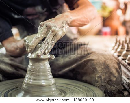 Hands of a potter, making pottery on pottery wheel (potter, handmade, clay)