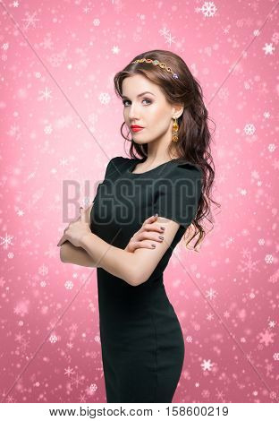 Beautiful brunette with luxury golden necklace over red winter background. Christmas concept.