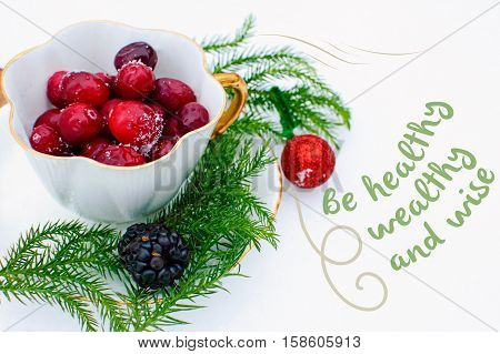 Seasons greetings Christmas card with words Be healthy, wealthy and wise written on white fresh snow background, and healthy winter berry and cranberry in a vintage tea cup with fir tree branches and shiny red ornament decoration New years wishes, Postcar