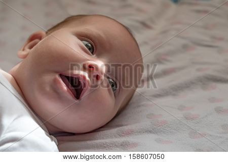 Cute newborn baby six months old in fashionable clothes looks with curiosity