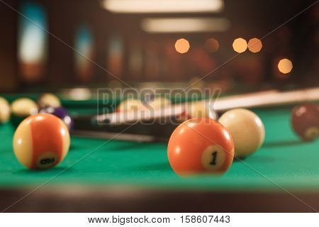 Billiard balls near by cue on the pool table.