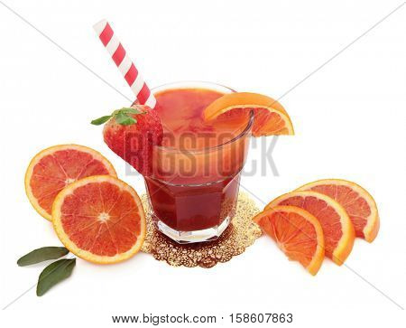 Blood orange fruit juice drink in a glass on a gold doilie with striped straw  over white background. High in vitamins, anthocyanins and antioxidants.