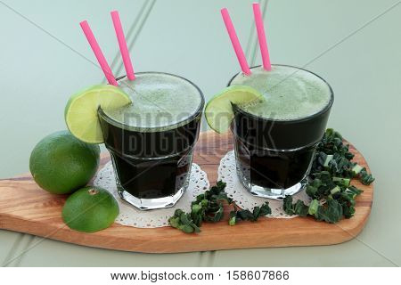 Kale and lime health drink with fresh vegetable leaves and fruit on an olive wood board over wooden green background. High in vitamins and antioxidants.