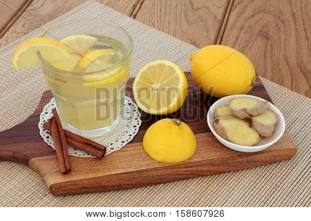 Cold and flu soothing remedy with hot lemon fruit drink, honey, ginger and cinnamon spice on bamboo over oak background.