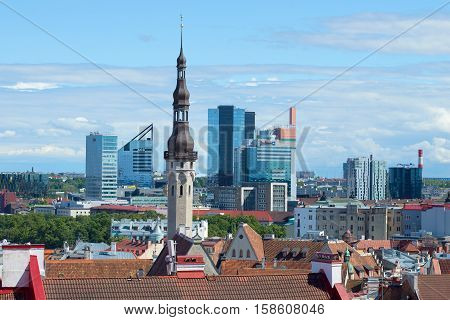TALLINN, ESTONIA - AUGUST 01, 2015: A spike of a medieval city town hall against the background of the modern city. Tallinn, Estonia