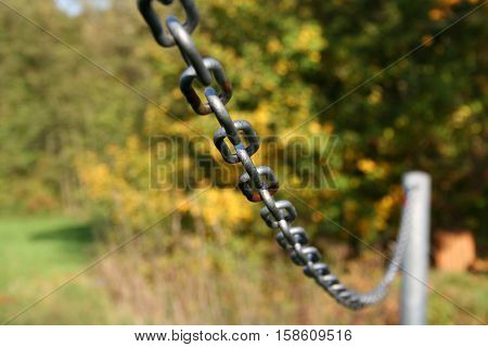 Sturdy chain of iron on a lawn / Robust iron chain defines green of a lawn.