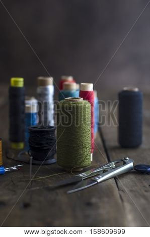 Bobbins with colorful threads on old wooden table background shallow depth of field.