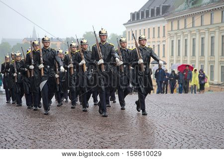 STOCKHOLM, SWEDEN - AUGUST 29, 2016: The group of royal guardsmen marching in the rain. A guard divorce ceremony fragment at the Royal palace