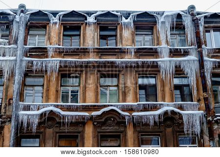 Old clock and Long Icicles Hanging from Roof down to Red Brick Wallamazing beautiful house with long icicles on it