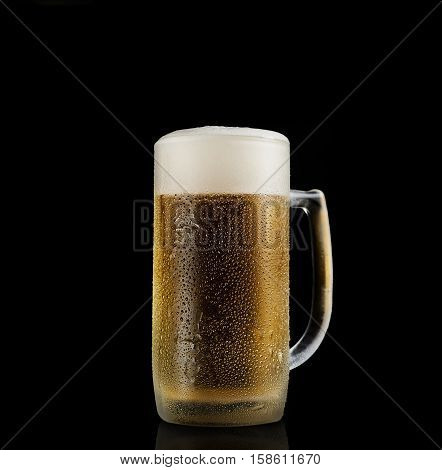 Pint of cold foamy beer on a black background