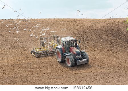 Large view on the tractor harrowing the field in spring season