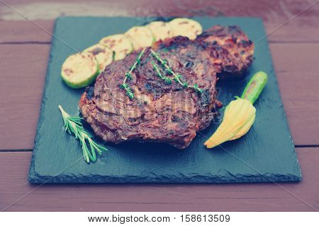 Rib eye steak with vegetables a on slate plate, toned image