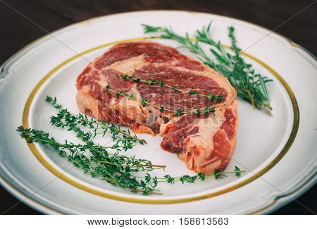 Rib eye steak in a rustic plate on wooden table, toned image