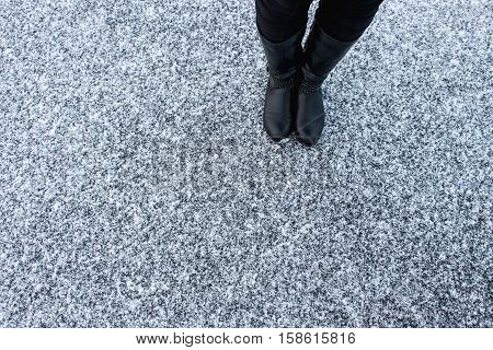 Women black leather boots standing on rough snow background. Gritty snow covered asphalt surface. Textplace. Top view