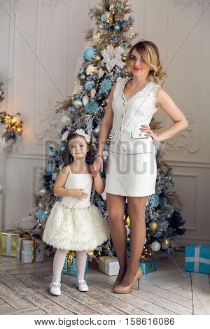 mother and daughter three years standing at the Christmas tree decorated with toys and gifts