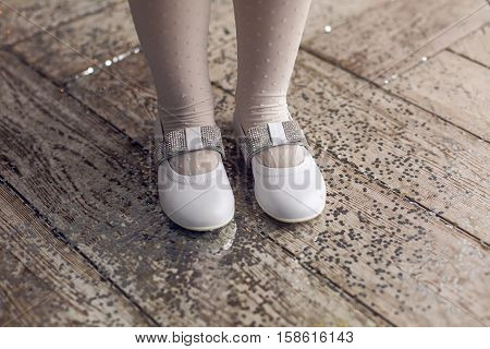 feet in white shoes little girl three years old in a white dress