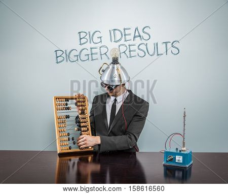 Big  ideas  bigger text on blackboard with businessman and abacus