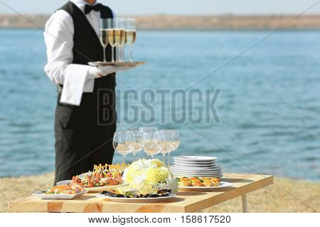 Table served for buffet catering party outdoors near river